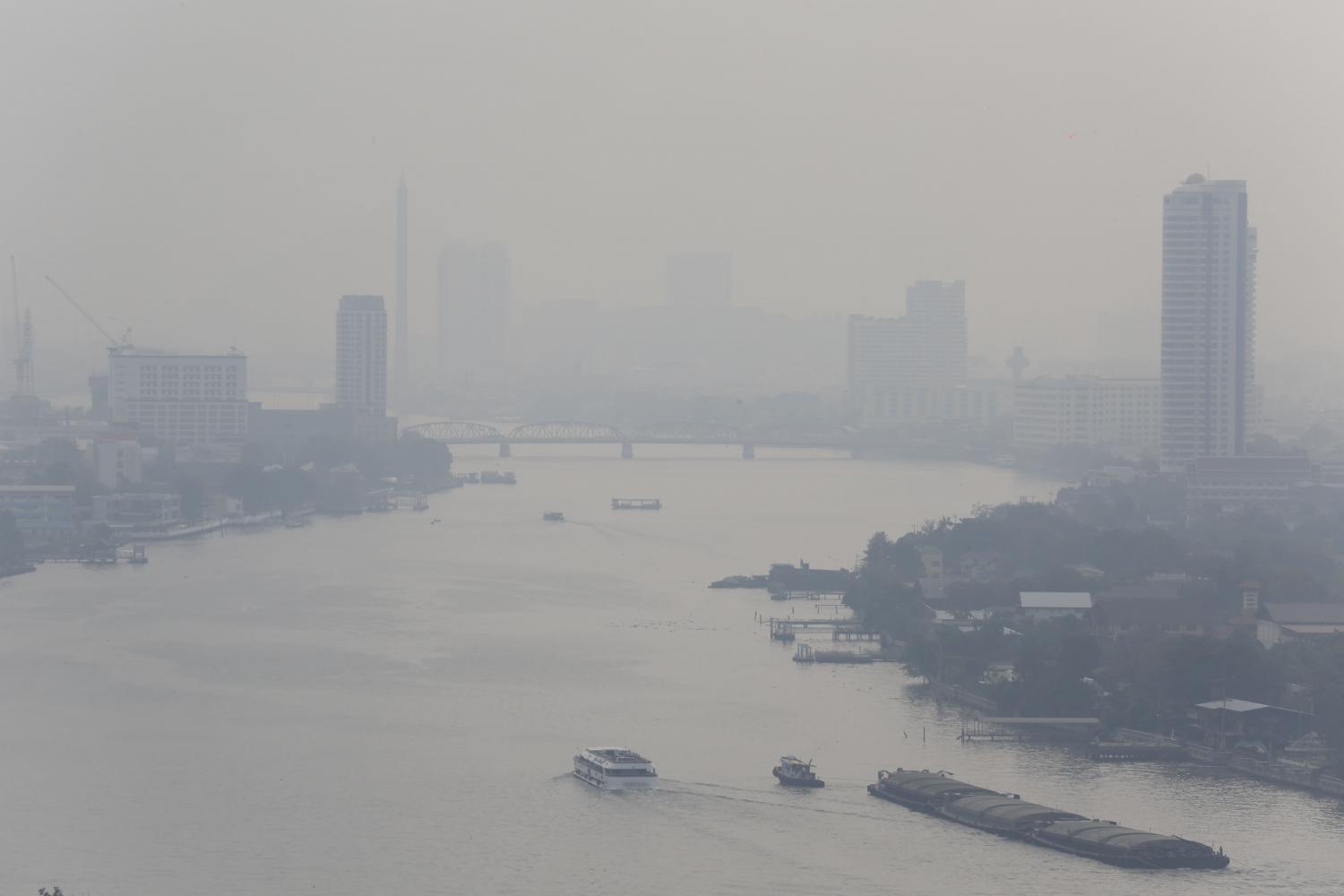 The Chao Phraya River is blanketed with thick haze on Monday as hazardous ultra-fine dust levels in the air exceeded so-called safe levels in many parts of Bangkok. Residents were warned to wear masks outdoors. (Photo by Pornprom Satrabhaya)