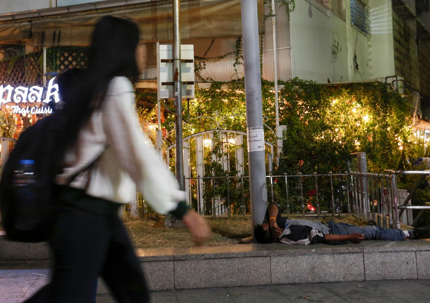 A woman walks past a homeless man in Bangkok. Thailand's inequality is among the highest in the world. (Photo by Pattarapong Chatpattarasill)