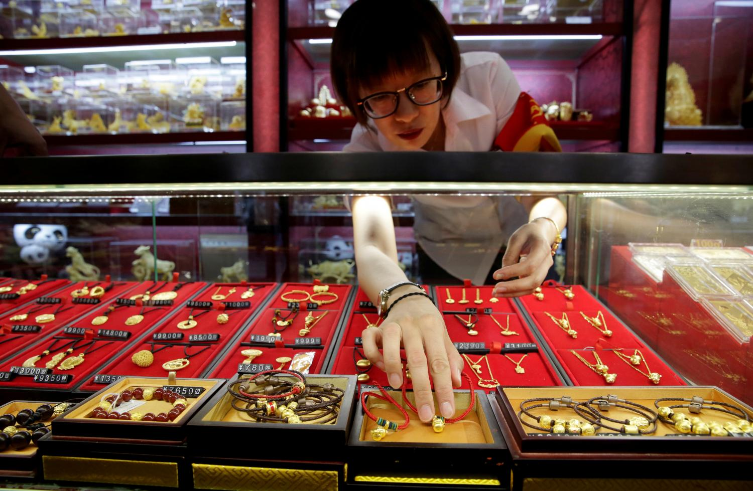 A sales assistant takes out gold ornaments for a customer at Caibai Jewelry store in Beijing. (Reuters photo)