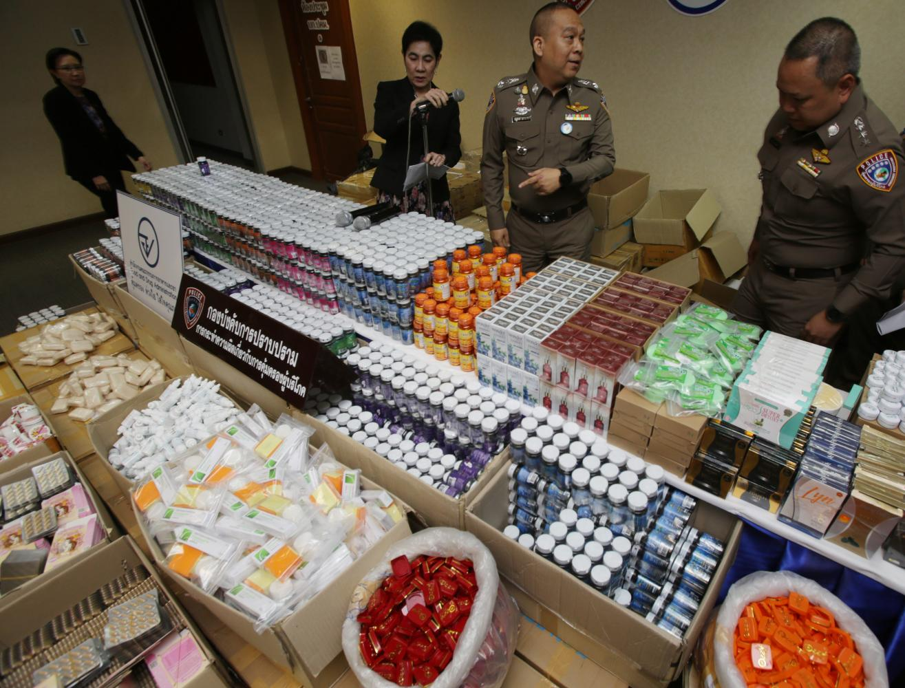 Police display more than 15,000 items of seized counterfeit herbal medicines, cosmetics and supplementary foods at a press briefing at the Consumer Protection Police Division in Bangkok on Tuesday. Apichit Jinakul