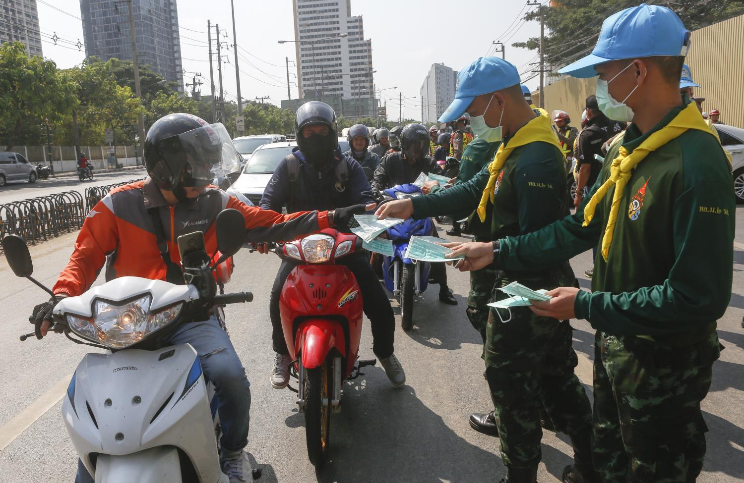 Royally sponsored 'Jit Arsa' volunteers from the 2nd Cavalry Division in Bangkok give away masks to commuters passing Queen Sirikit National Convention Centre on Ratchadaphisek Road amid concerns over PM2.5 levels and the air pollution crisis. (Photo byPattarapong Chatpattarasill)
