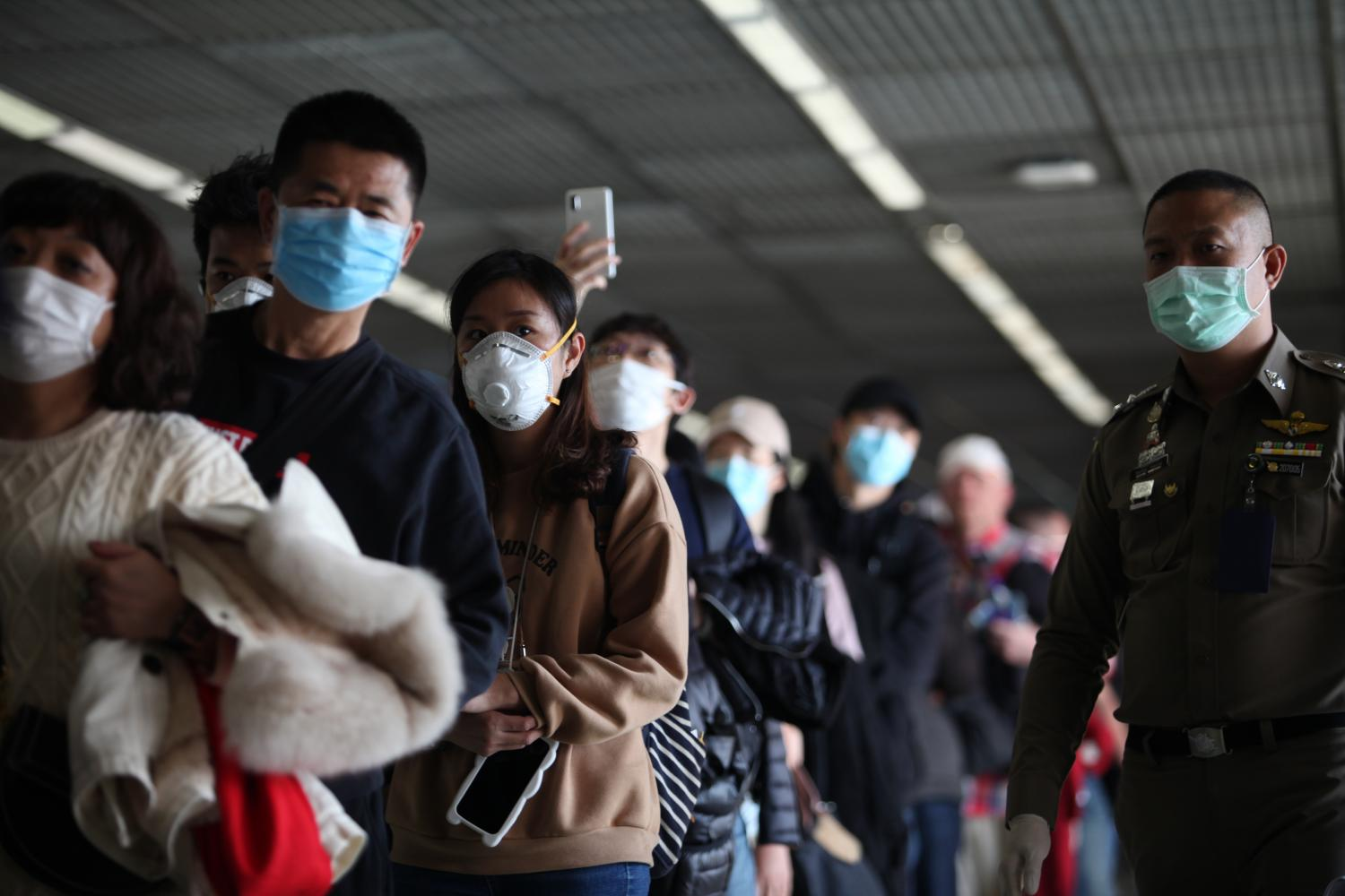 Initial check: Passengers arriving from China stand in a long queue as they wait to walk through a thermal scanner at Don Mueang Airport, which is intensifying the screening of passengers by checking them for signs of fever.