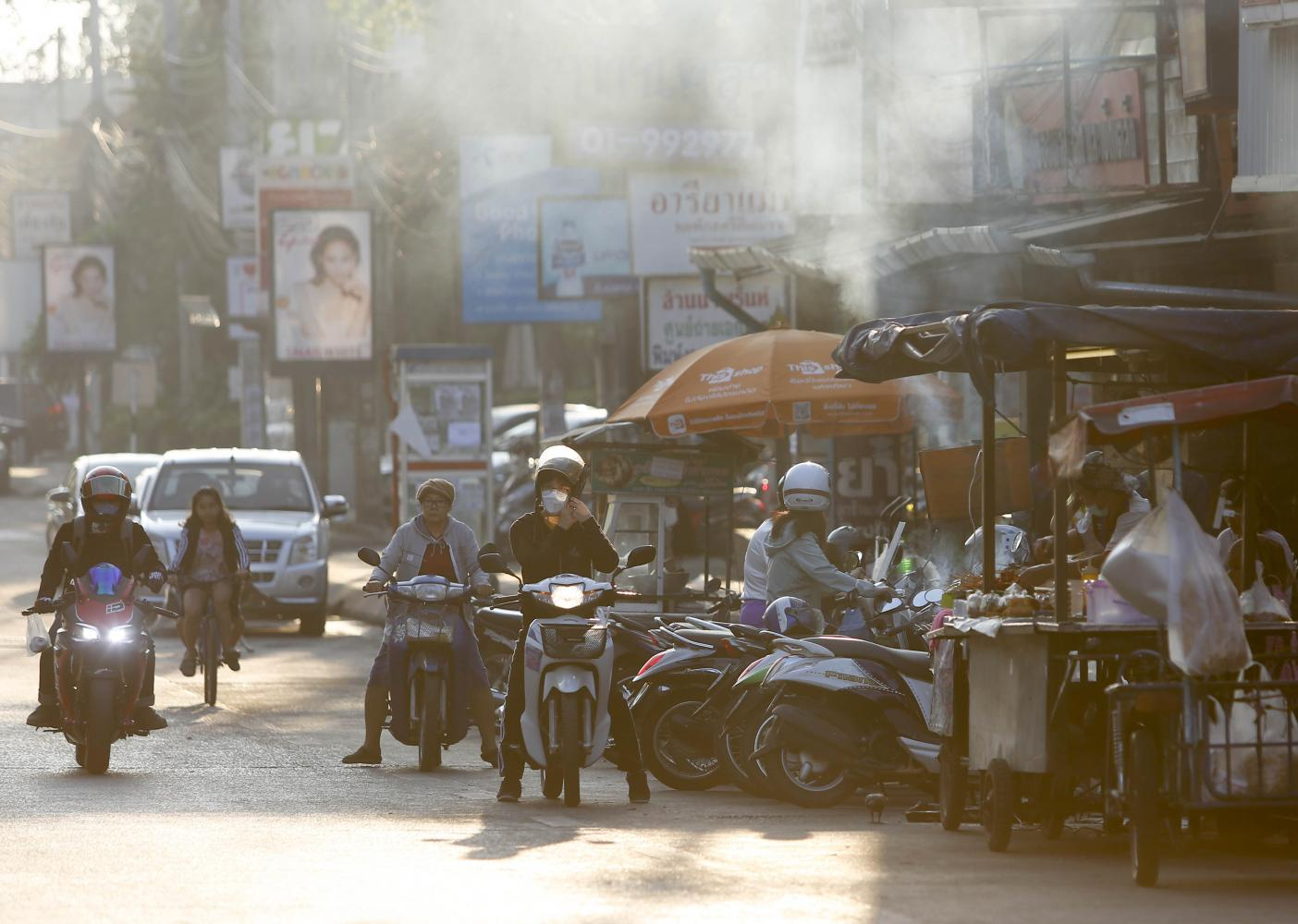 DAILY GRIND: Residents brave the dust and fumes on a hazy morning in Chiang Mai. PM2.5 remained present in the air at unsafe levels in many parts of the North on Saturday.