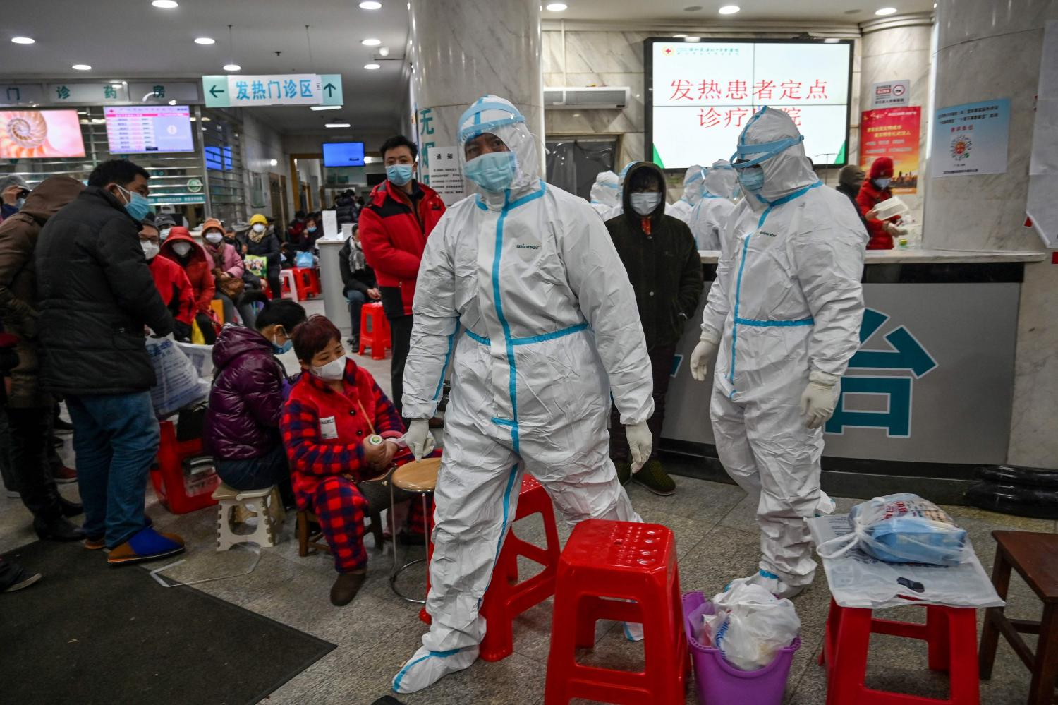 Medical staff members wearing protective clothing to help stop the spread of the deadly virus which began in Wuhan, walk next to patients waiting for medical attention at the Wuhan Red Cross Hospital.(AFP photo)