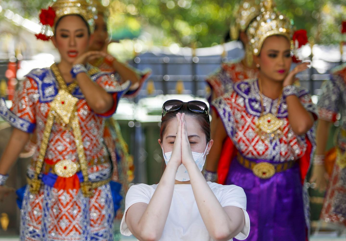 A Chinese tourist at the Erawan shrine at Ratchaprasong intersection prays while wearing a face mask. (Photo by Pattarapong Chatpattarasill)