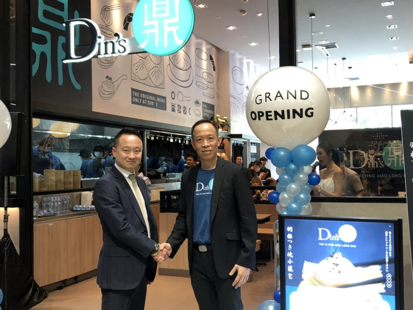 Mr Boonyong, right, shakes hands with Yuta Ogisu, chief executive of Food Buddies Co, at the grand opening of Din's, the 16th restaurant brand under Zen Corporation.