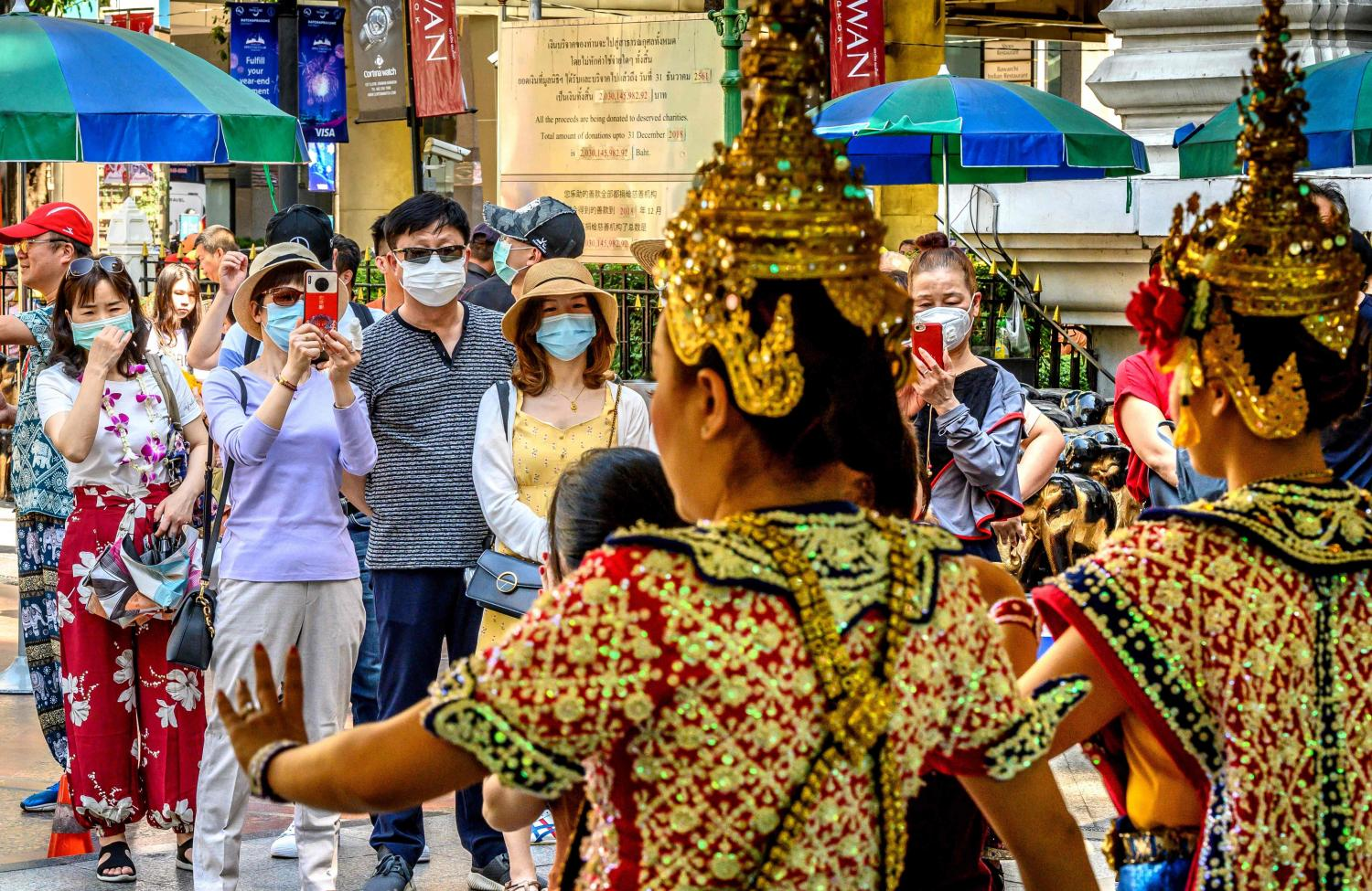 Chinese tourists with face masks watch a traditional Thai dance at Erawan Shrine, a popular spiritual landmark in Bangkok. AFP