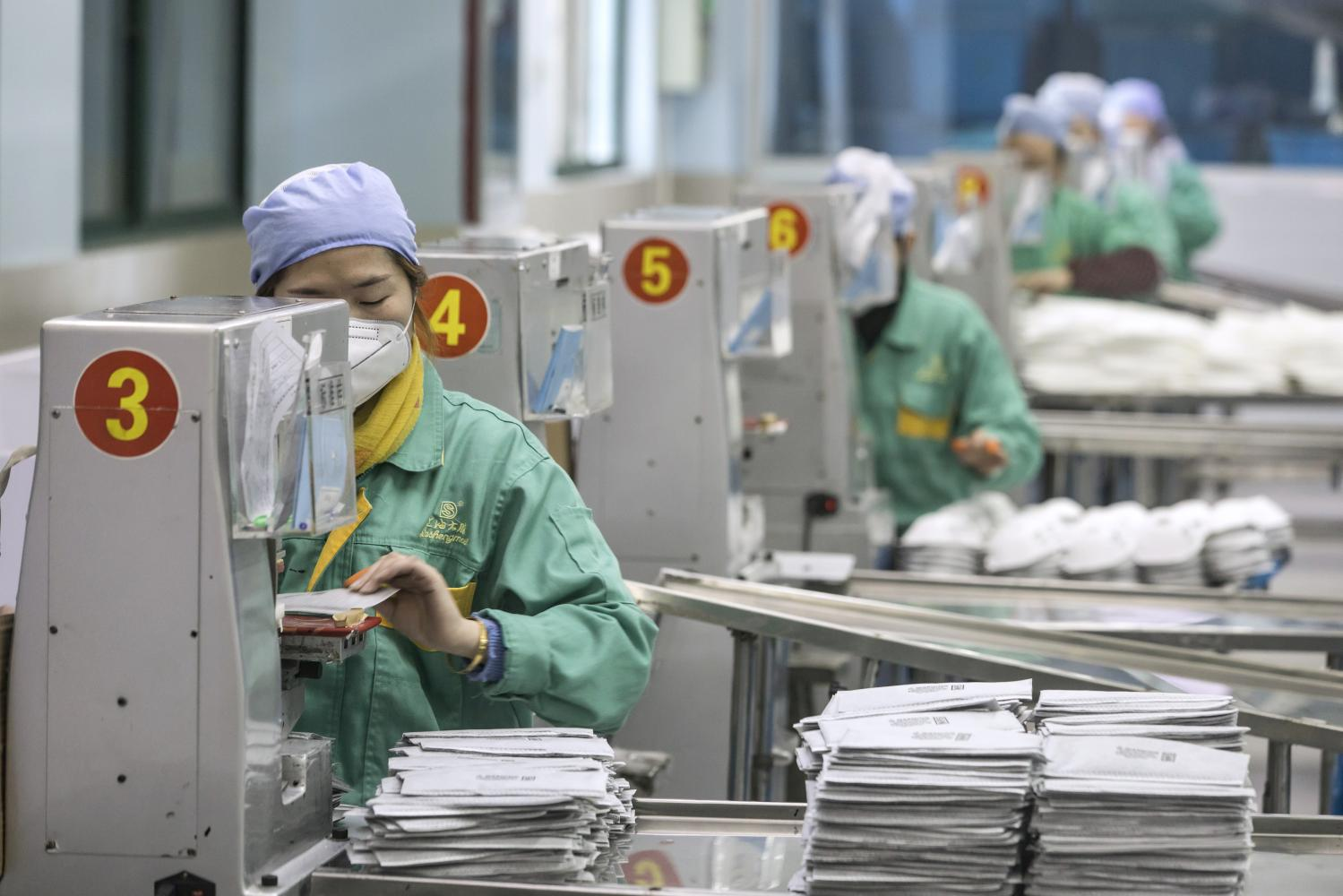 Employees work on the assembly line to make protective masks at a factory operated by Dasheng Health Products Manufacturing Co. in Shanghai yesterday. People across the globe are stockpiling facial masks to protect themselves from the new coronavirus.