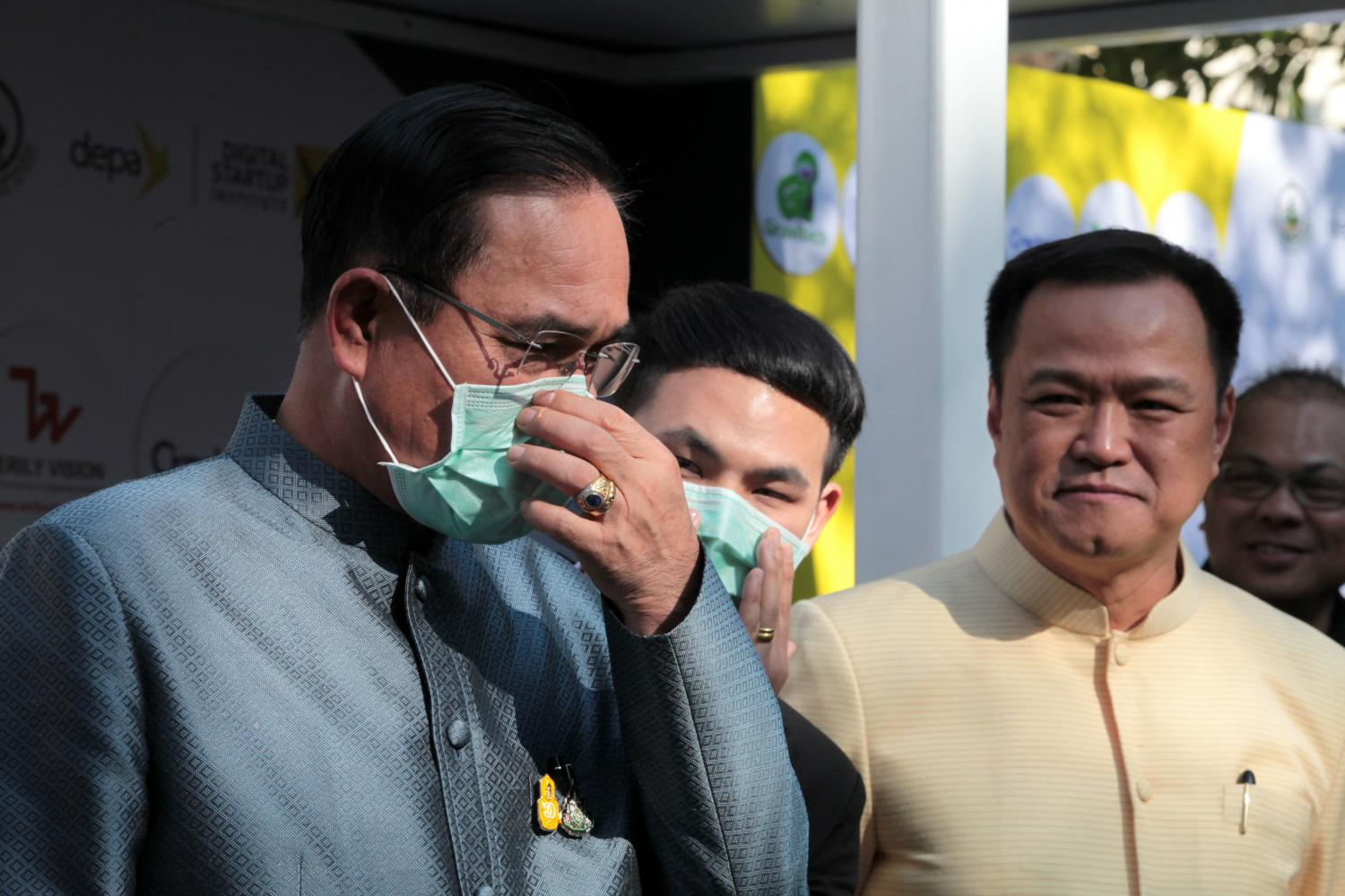 Prime Minister Prayut Chan-o-cha, left, demonstrates how to wear a face mask as a guard against the coronovirus and PM2.5 dust at Government House last week as Public Health Minister Anutin Charnvirakul, right, looks on. CHANAT KATANYU