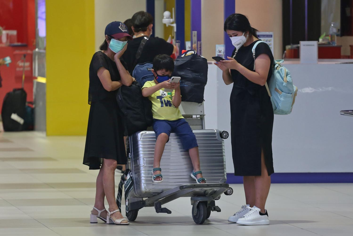 Passengers wear masks at Don Mueang airport to help prevent the spread of coronavirus.(Photo by Varuth Hirunyatheb)