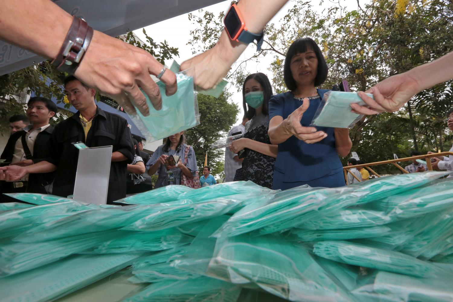 People buy face masks at one of two makeshift stalls set up near Government House yesterday morning. As many as 20,000 masks were reportedly snapped up in half an hour. Sales of the masks — a box of 10 for 25 baht — were limited to one set per person. (Photo by Chanat Katanyu)
