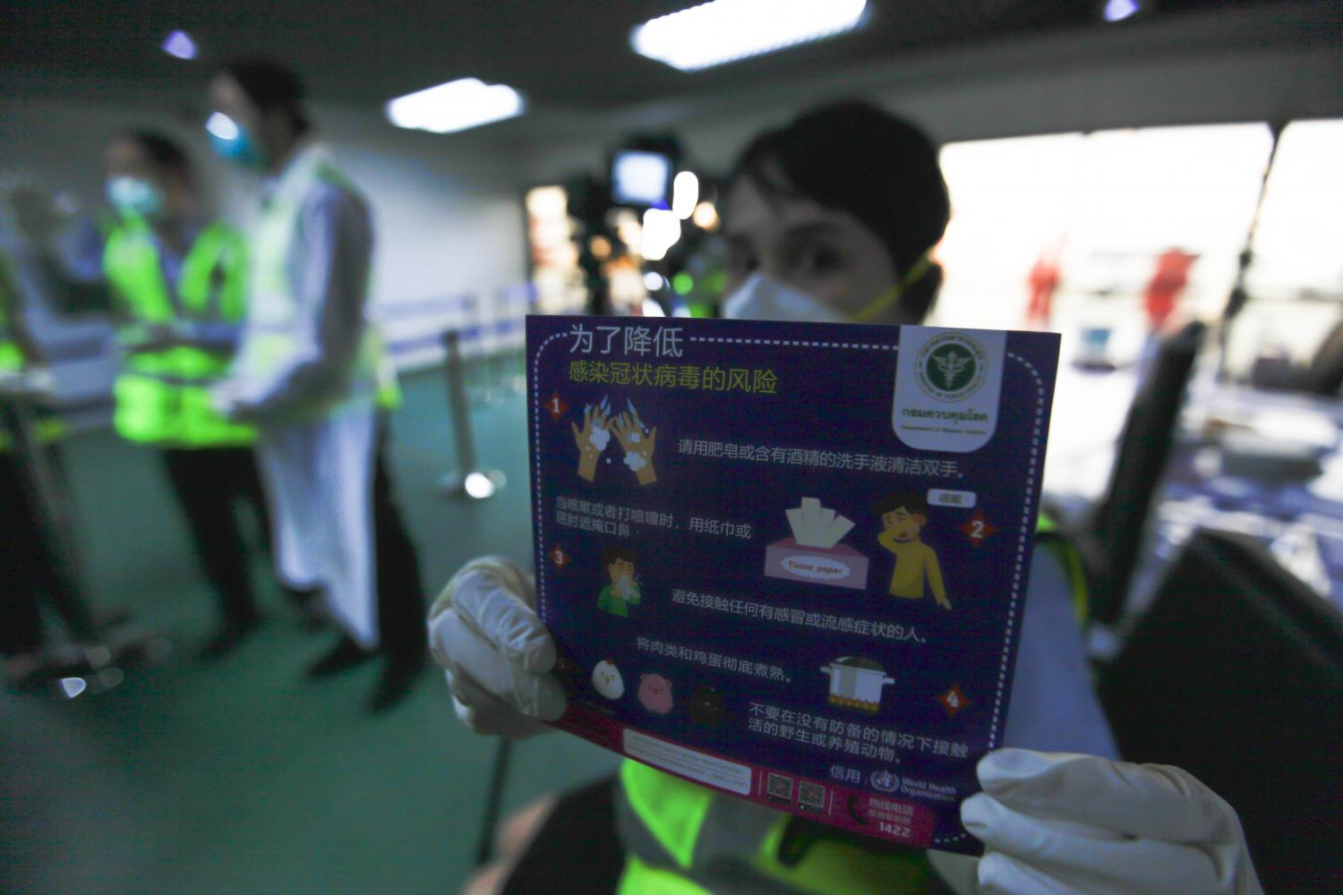 An official at Don Mueang airport holds a health advisory card written in Chinese at the Tier 6 passenger screening area for all arrivals from China. Those suspected of carrying coronavirus will be isolated and transferred to a hospital. Pattarapong Chatpattarasill