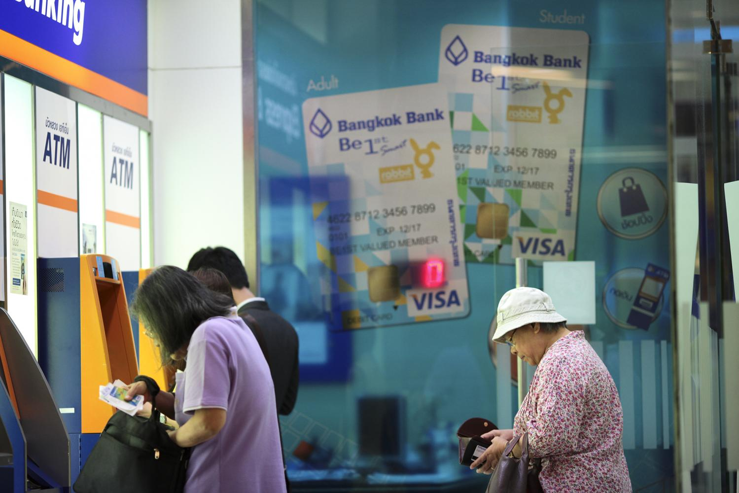Customers use ATMs at a Bangkok Bank branch in the Rama IX area. Banks have waived fees for customers to ease their financial burden. (Photo by Patipat Janthong)