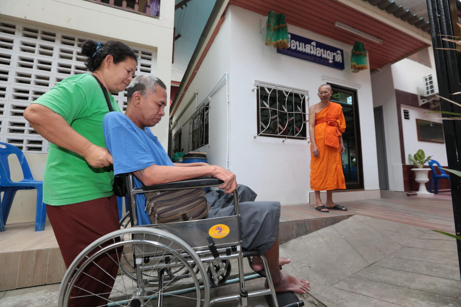 A woman wheels a patient into accommodation at Wat Ammarinthararam Worawihan, where low-income patients of nearby Siriraj Hospital can stay for free along with their relatives. Chanat Katanyu