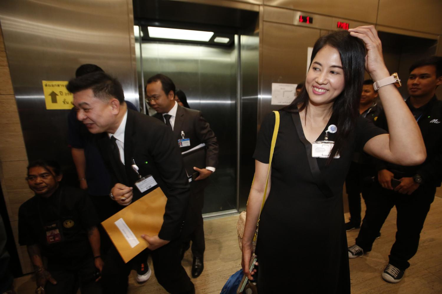 Pareena Kraikupt, Palang Pracharath Party MP for Ratchaburi, smiles on Wednesday as she faces a parliamentary press pack waiting to question her about her alleged land encroachment in Ratchaburi's Chom Bung district.(Photo by Pornprom Satrabhaya)