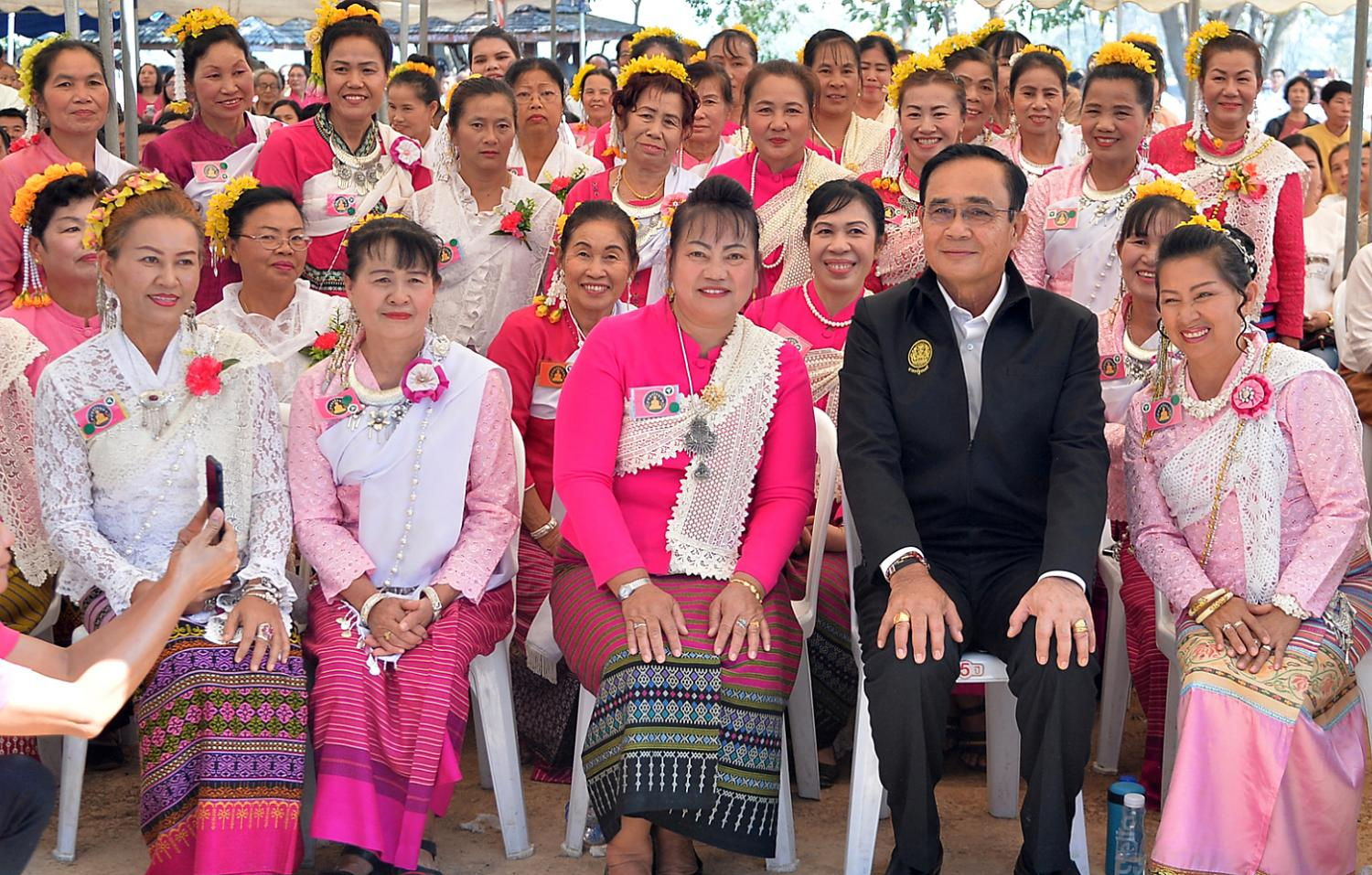 Prime Minister Prayut Chan-o-cha takes a group photo with women in traditional outfits who welcomed him to the local product fair in Phayao on Wednesday.(Government House photo)
