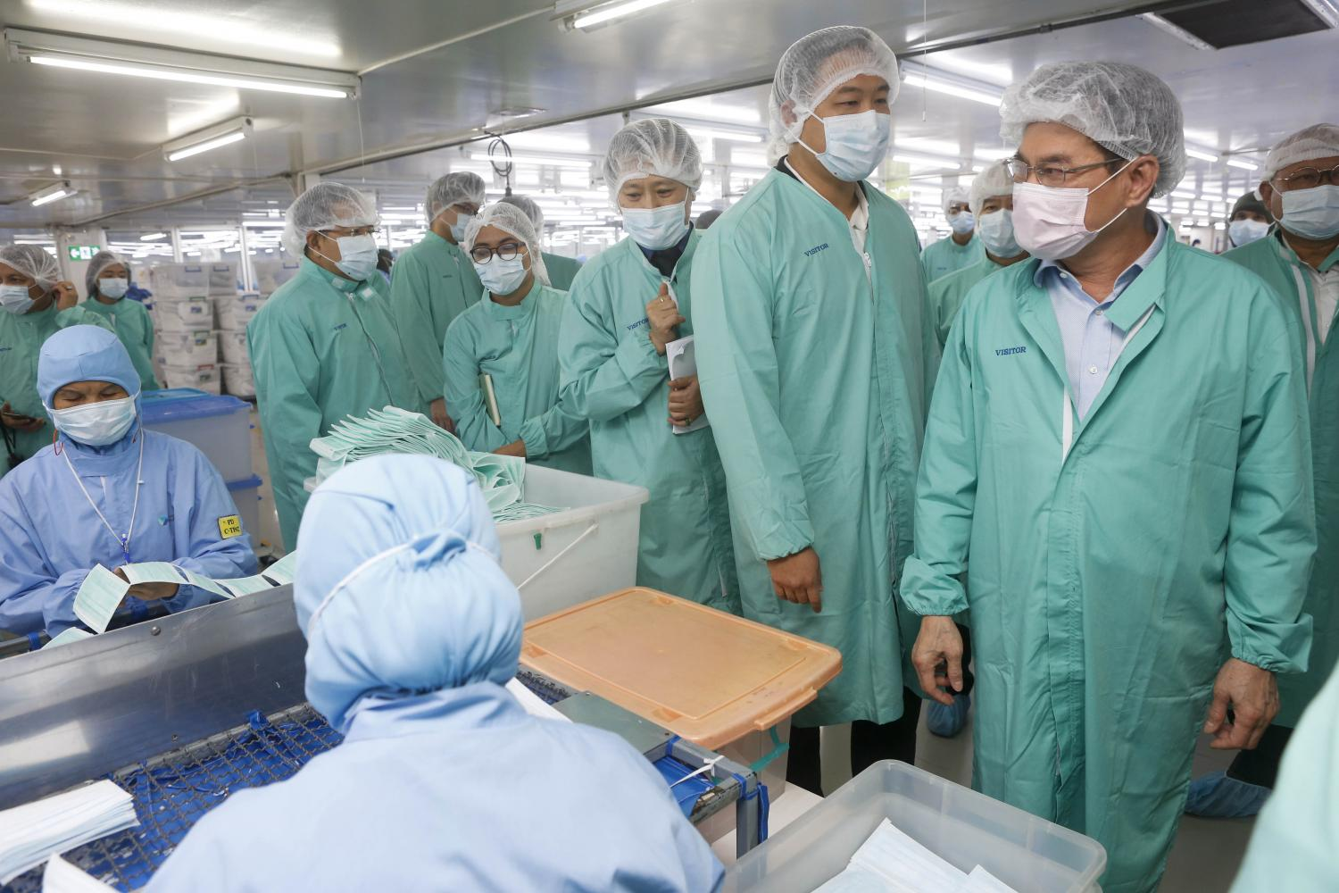 Commerce Minister Jurin Laksanavisit (right) visits a face mask factory in Nonthaburi's Pak Kret district. (Photo by Pattarapong Chatpattarasill)