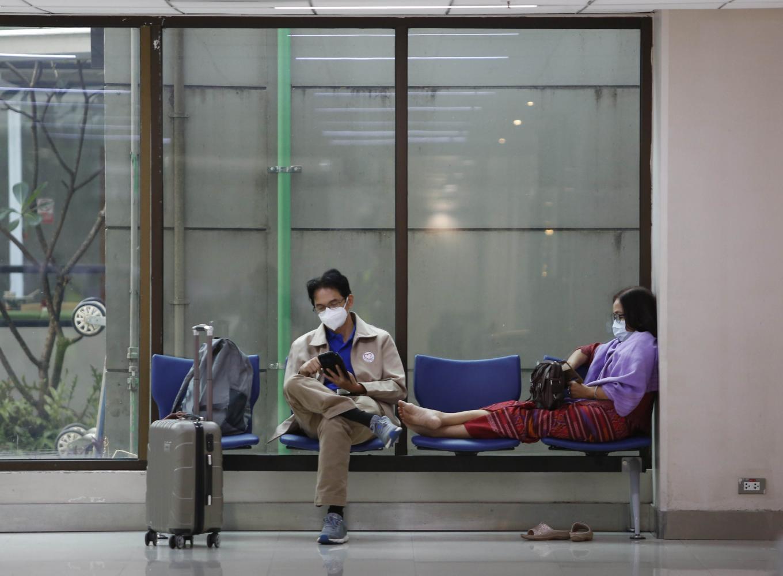 Passengers wearing face masks to protect themselves against the coronavirus wait at a terminal at Don Mueang airport in Bangkok.PATTARAPONG CHATPATTARASILL