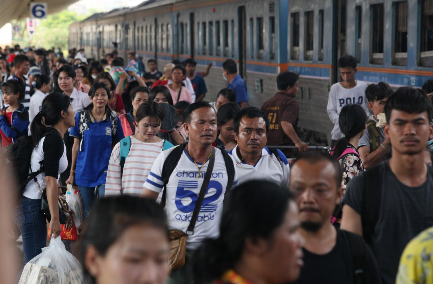 Passengers carry luggage at Hua Lamphong station in Bangkok after using the free train service. Thailand needs to get serious about tackling inequality, says economist Somchai Jitsuchon. APICHIT JINAKUL
