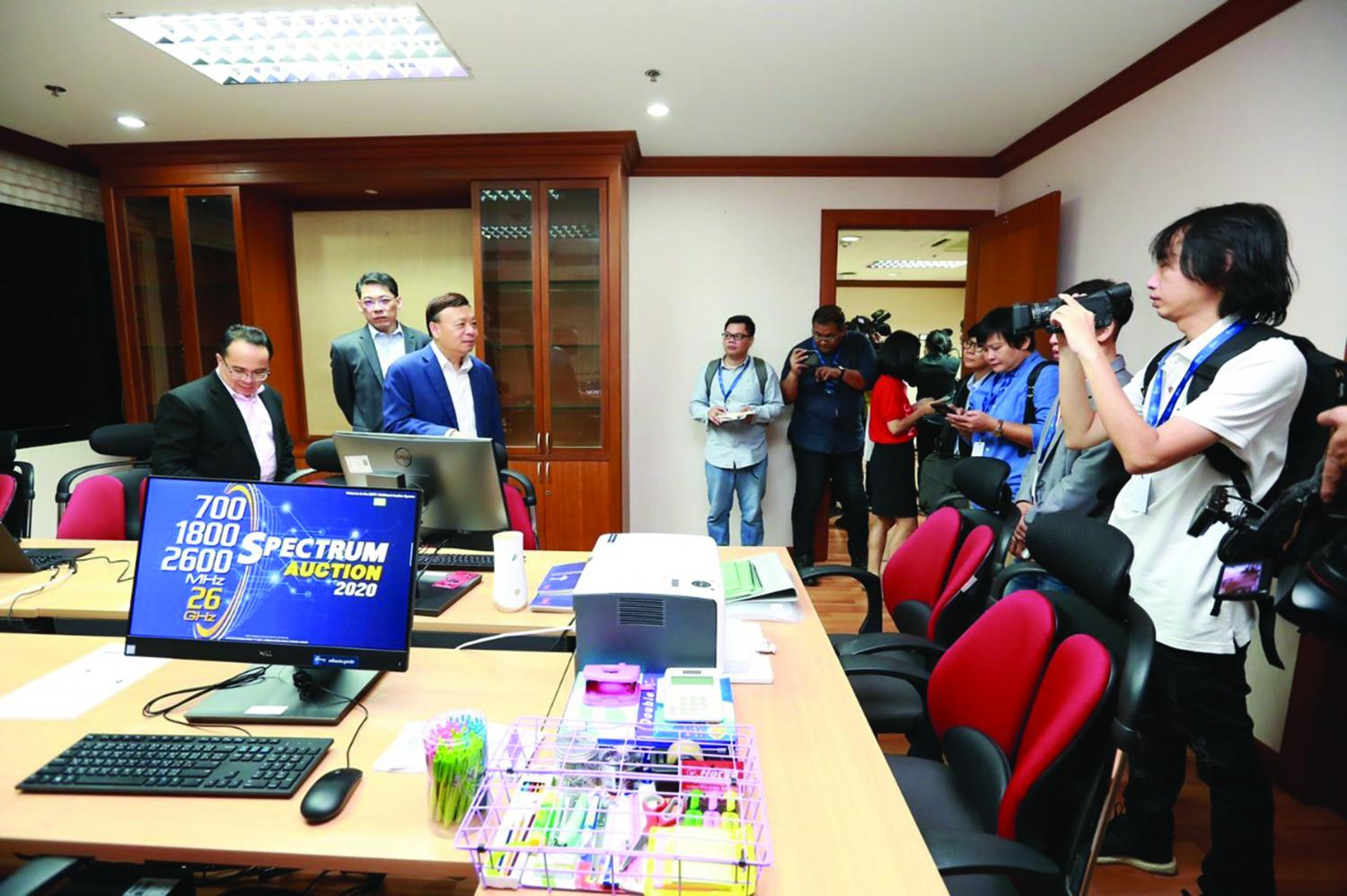 Takorn Tantasith, secretary-general of the National Broadcasting and Telecommunications Commission (third from left) briefs journalists on the 5G spectrum licence auction taking place on Sunday. (National Broadcasting and Telecommunication Commission)