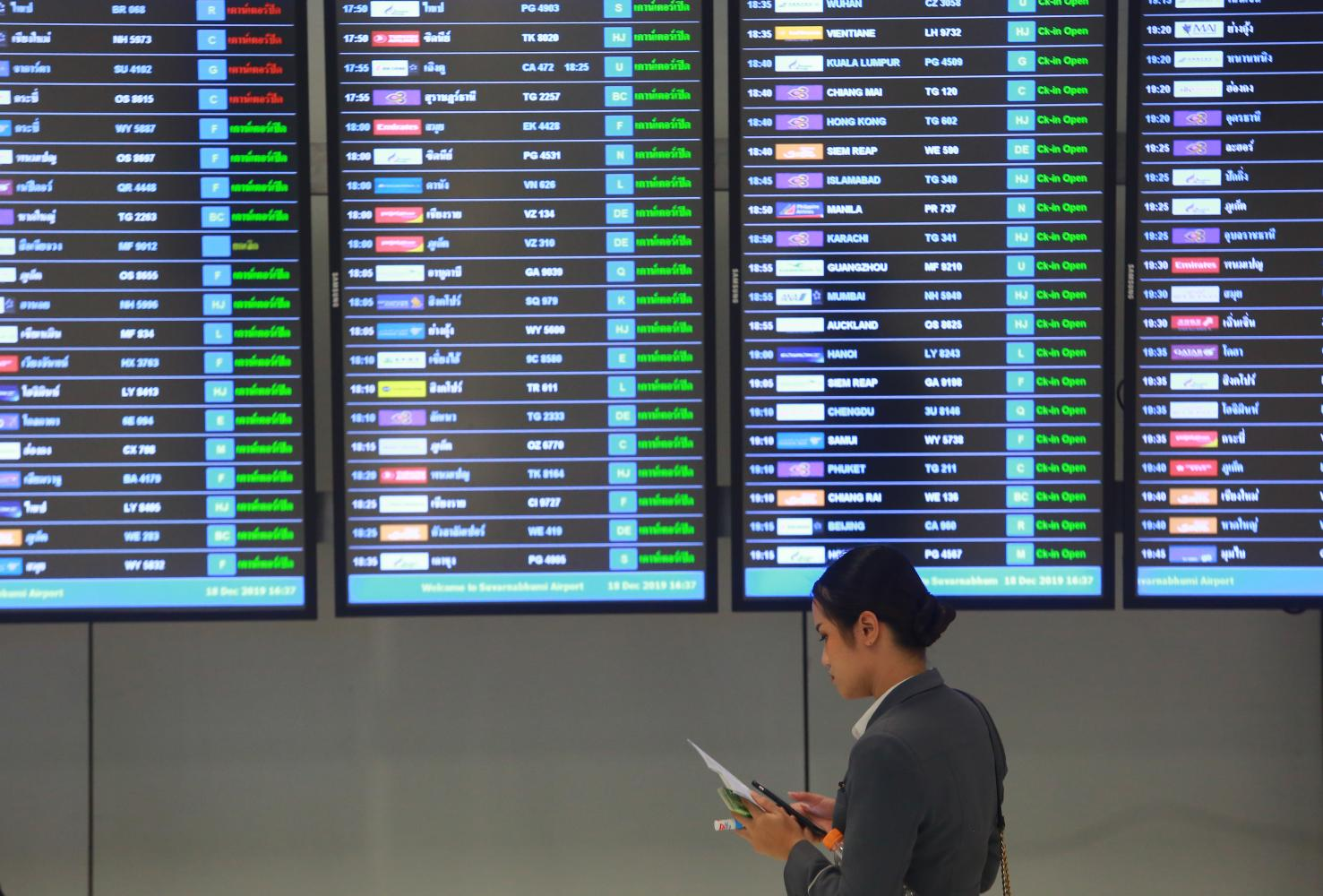 A woman stands at a display of flight information at Suvarnabhumi airport. South Korean airlines have suspended more flights to Thailand.