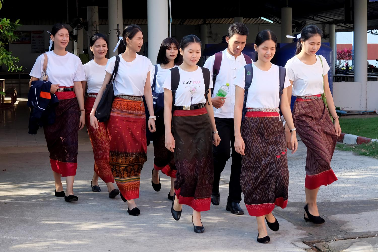 University students are seen wearing 'phasin' as they walk to their classes. Many students have taken to experimenting with phasin as a uniform, which is gaining popularity in universities in the lower Northeast. Phitsanu Thepthong