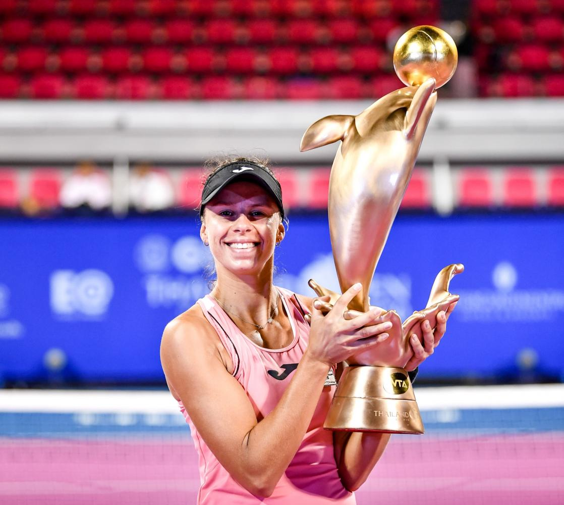 Magda Linette celebrates with the winner's trophy.