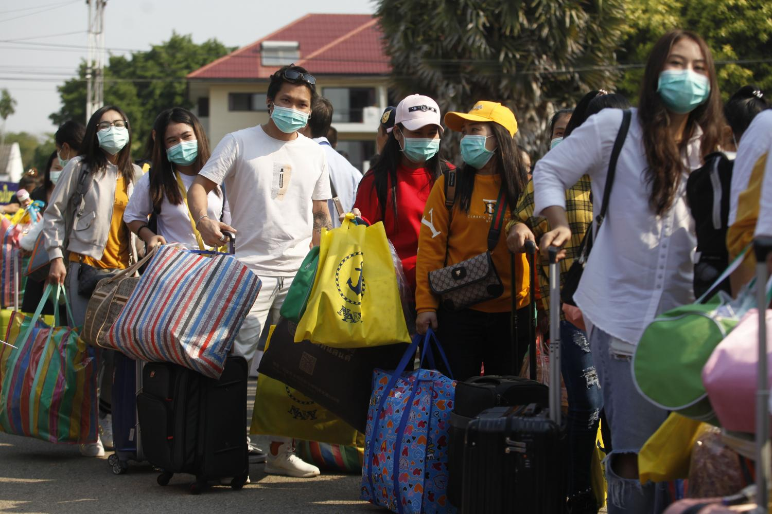 A total of 137 people walk single-file out of the quarantine facility at the Sattahip Naval Base in Chon Buri on Wednesday. (Photo by  Wichan Charoenkiatpakul)