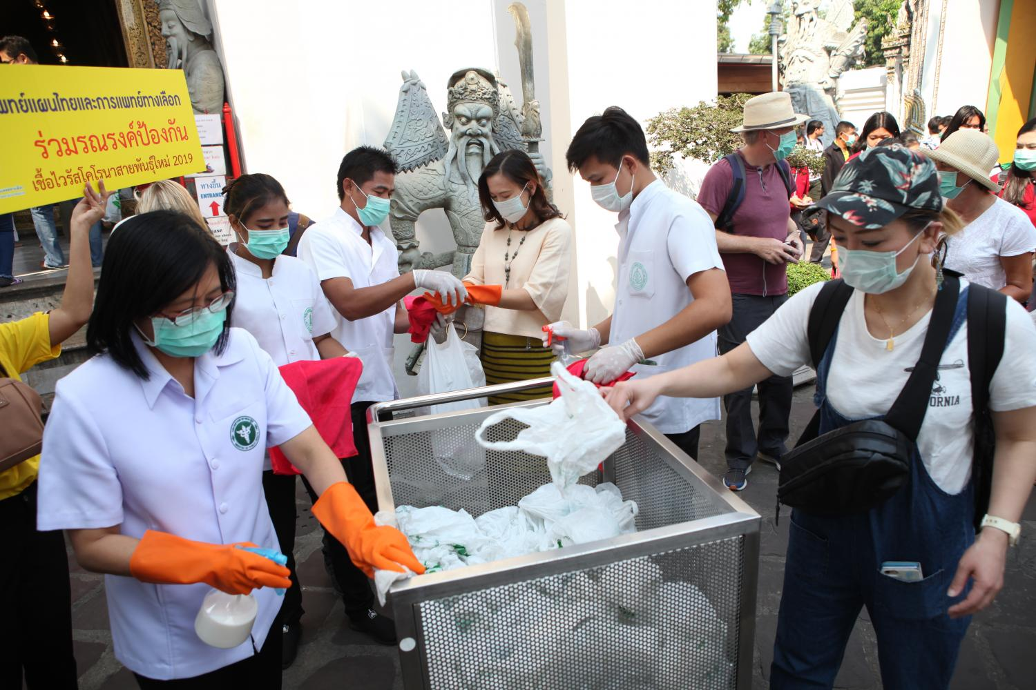 Staff at Wat Pho disinfect bags used by visitors to carry shoes in the Reclining Buddha Hall, part of measures to fight Covid-19.(Photo by Arnun Chonmahatrakool)