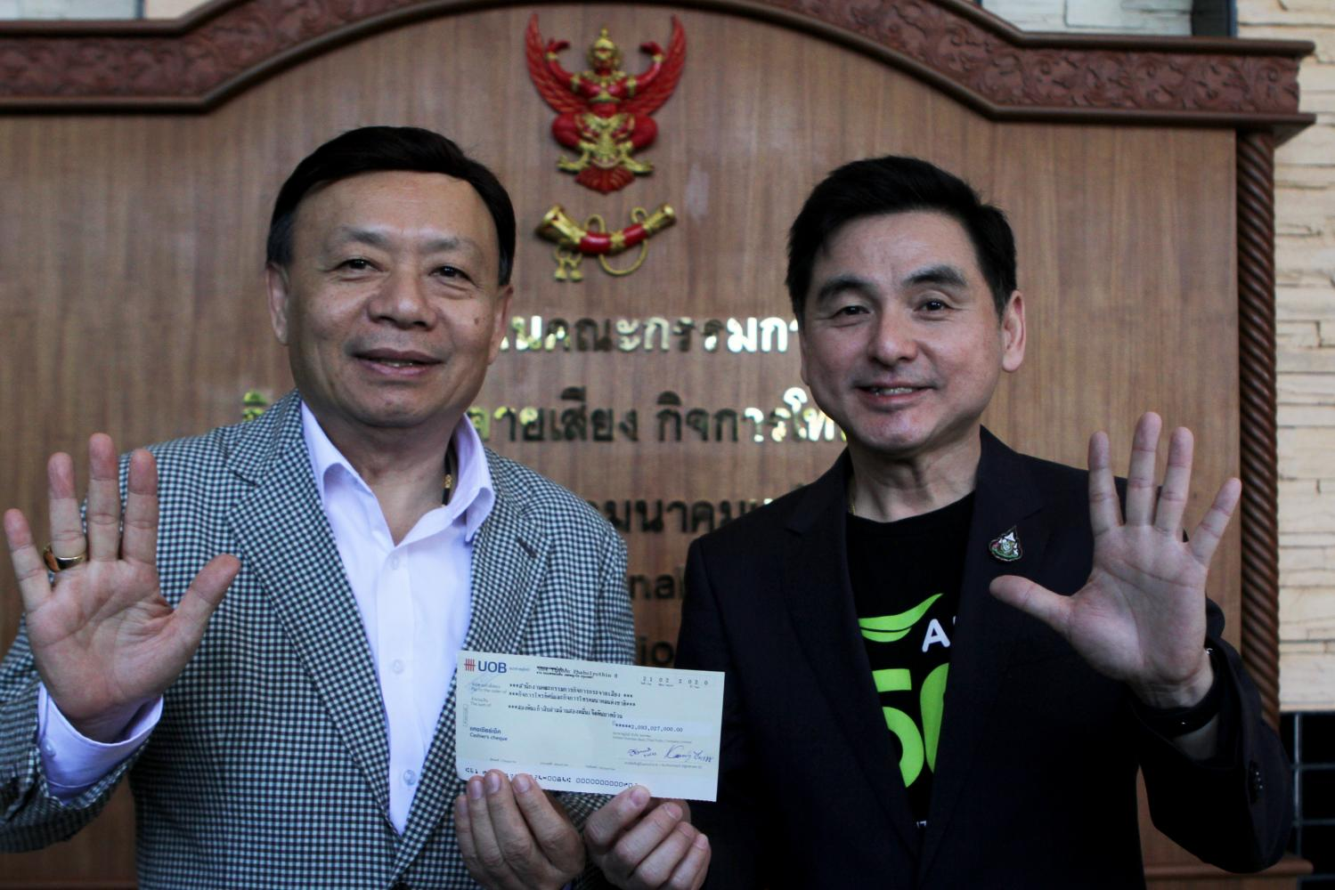 Mr Somchai (right) makes the first instalment payment for 2600MHz spectrum and receives the licence from NBTC secretary-general Takorn Tantasith.