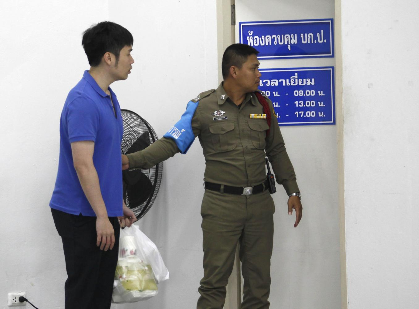 A son of former deputy commerce minister Pol Lt Col Banyin Tangpakorn waits for permission to visit his father at the Crime Suppression Division HQ in Bangkok on Monday. (Photo by Pattarapong Chatpattarasill)