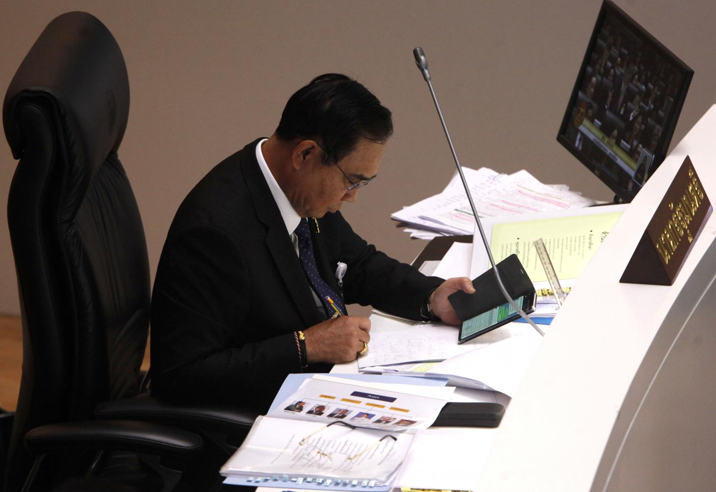 Prime Minister Prayut Chan-o-cha makes notes from his mobile phone in the chamber on the second day of the no-confidence debate on Tuesday.Wichan Charoenkiatpaku