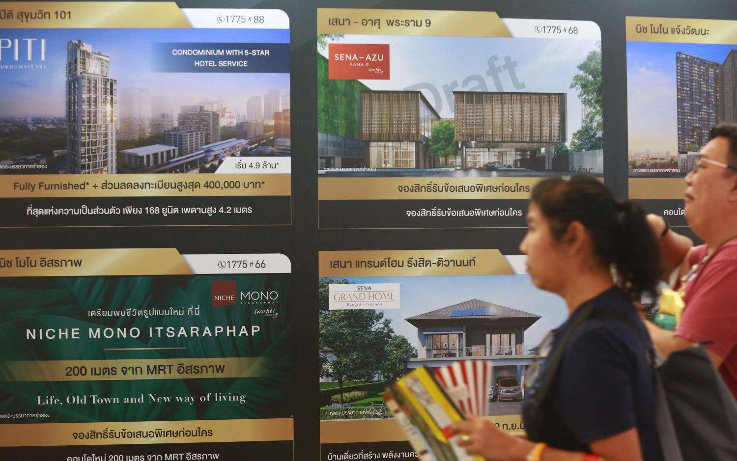 Potential buyers walk past advertisements at a property fair.(Photo by Somchai Poomlard)