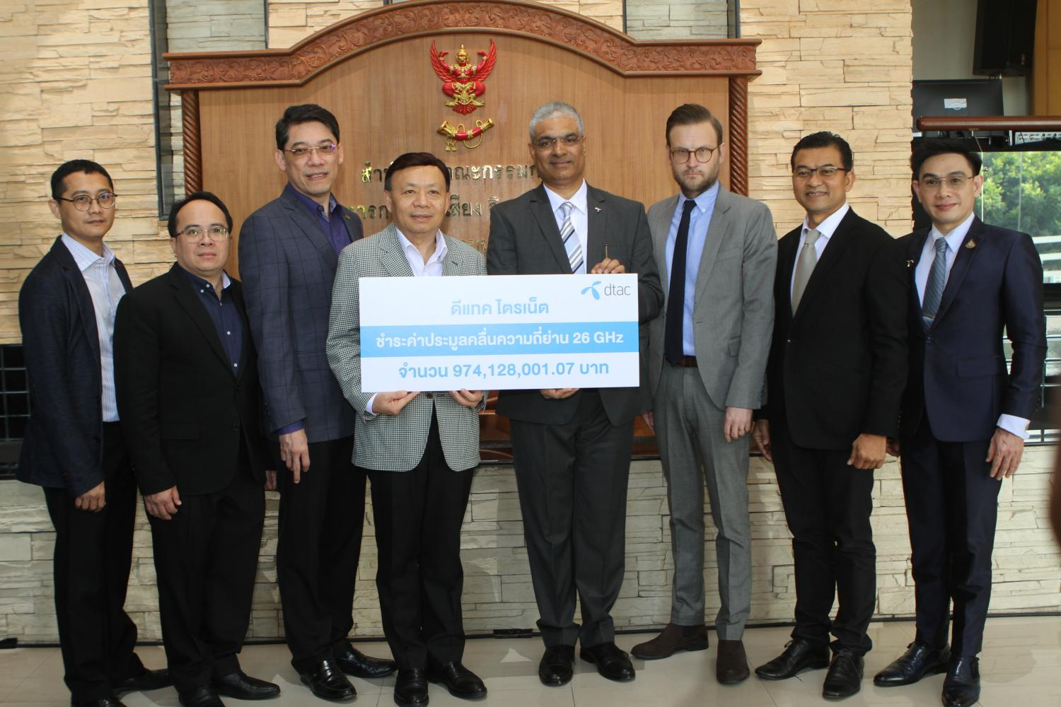 Mr Mehrotra hands a cheque for B974m to NBTC secretary-general Takorn Tantasith.Nutthawat Wicheanbut