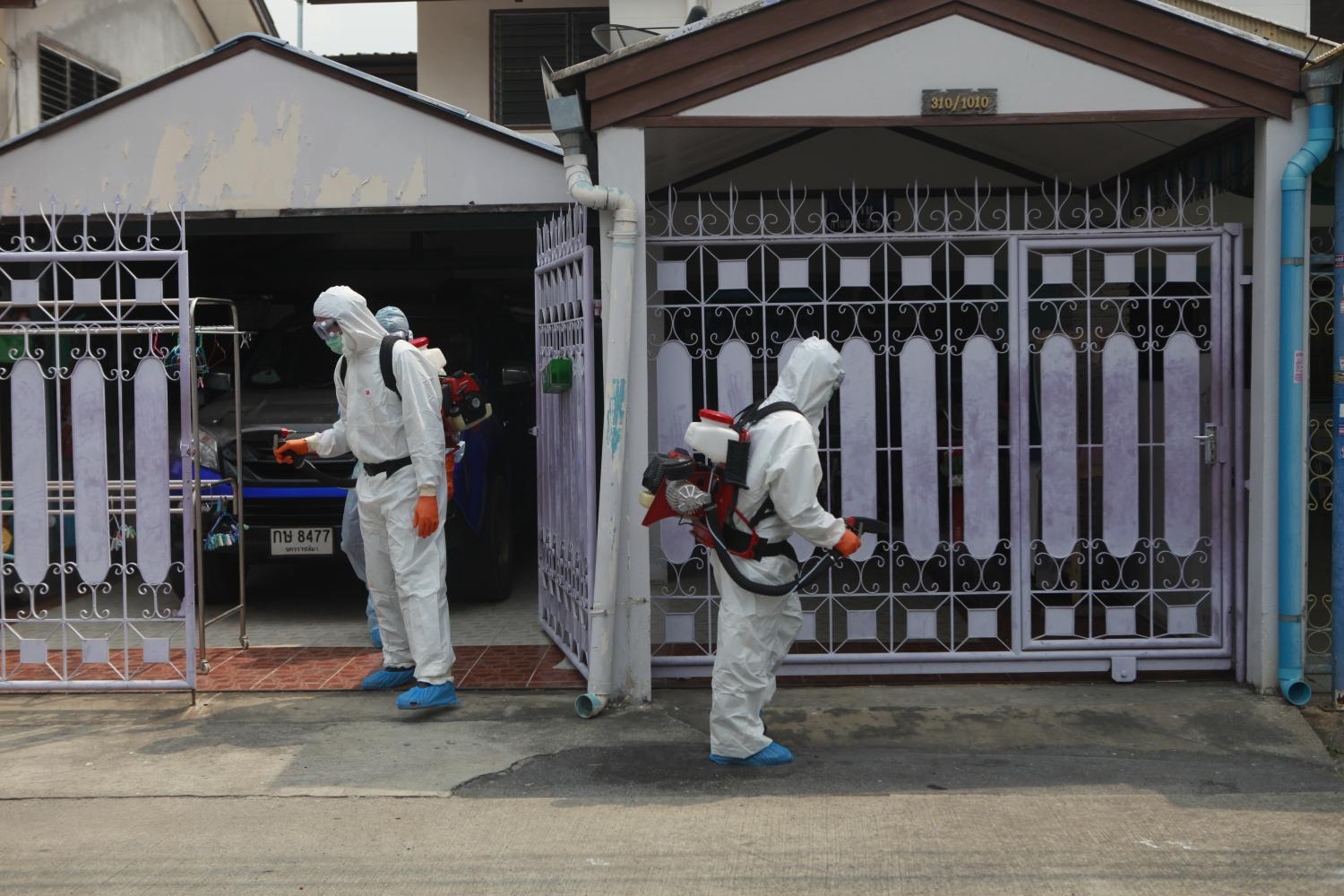 Workers from Don Muang district office disinfect the house of an elderly couple and their eight-year-old grandson who tested positive for Covid-19 after returning from a trip to Hokkaido, Japan. (Photo by Nutthawat Wicheanbut)