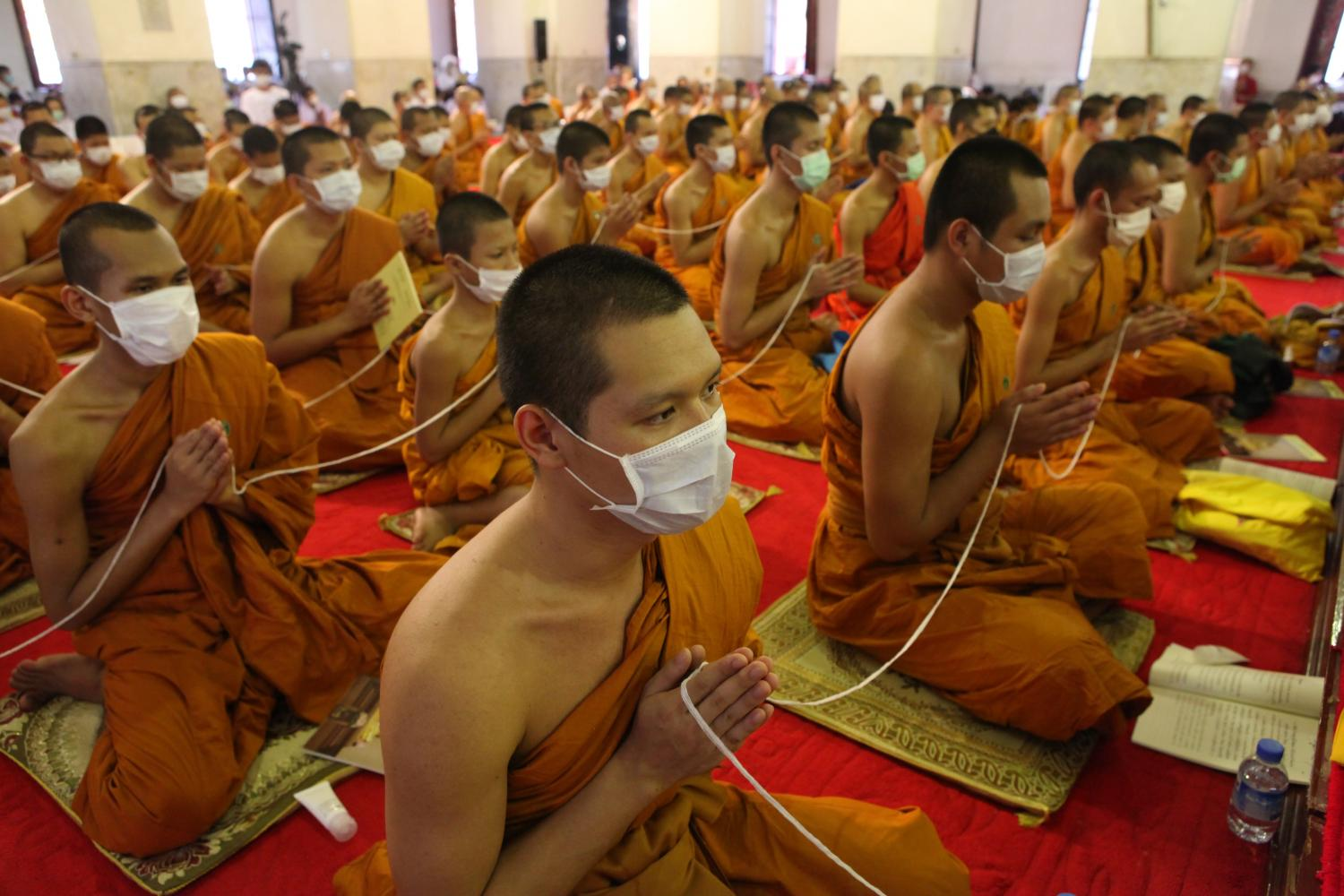 Monks from various temples on Sunday gather in the ubosot at Wat Maha That Yuwarat Rangsarit of Bangkok's Phra Nakhon district for evening prayer seeking blessings for the victims of the Covid-19 outbreak and an end to the rapid spread of the virus in all parts of the world.Arnun Chonmahatrakool