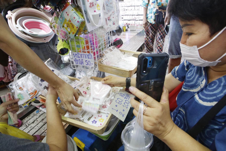 Customers buy washable facial masks made of fabric at Sampheng market in Bangkok at between 50 and 70 baht apiece.(Photo by Pornprom Satrabhaya)
