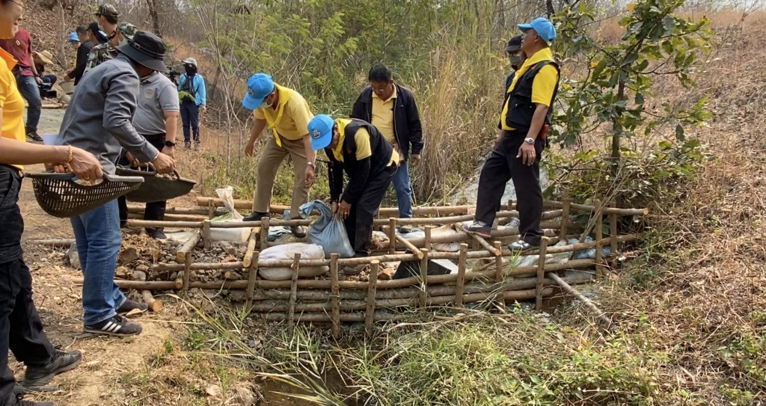 In preparation: Volunteers and residents in Lampang's tambon Phichai work together to build a dam to use as a firebreak to mitigate the impact of bushfires. The province suffers serious forest fires every year.