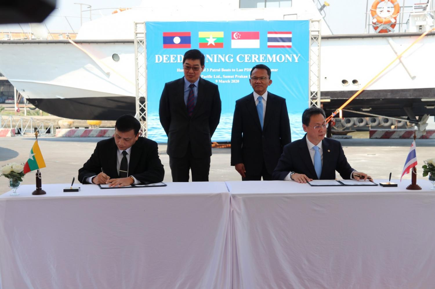 Thai Justice Minister Somsak Thepsutin, standing right, and Singaporean ambassador to Thailand Kevin Cheok, standing left, witness the handover of three patrol boats to Laos and Myanmar for the drug-suppression mission on the Mekong River.