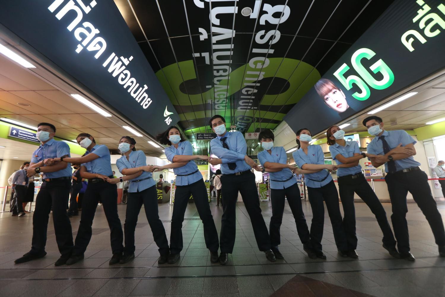 Staff of the BTS Skytrain operator dance at the launch of a campaign against Covid-19 by handing out masks and hand gel at the usually crowded Siam Station. The freebies were also given out at the National Stadium and Phaya Thai stations in inner Bangkok. (Photo by Varuth Hirunyatheb)