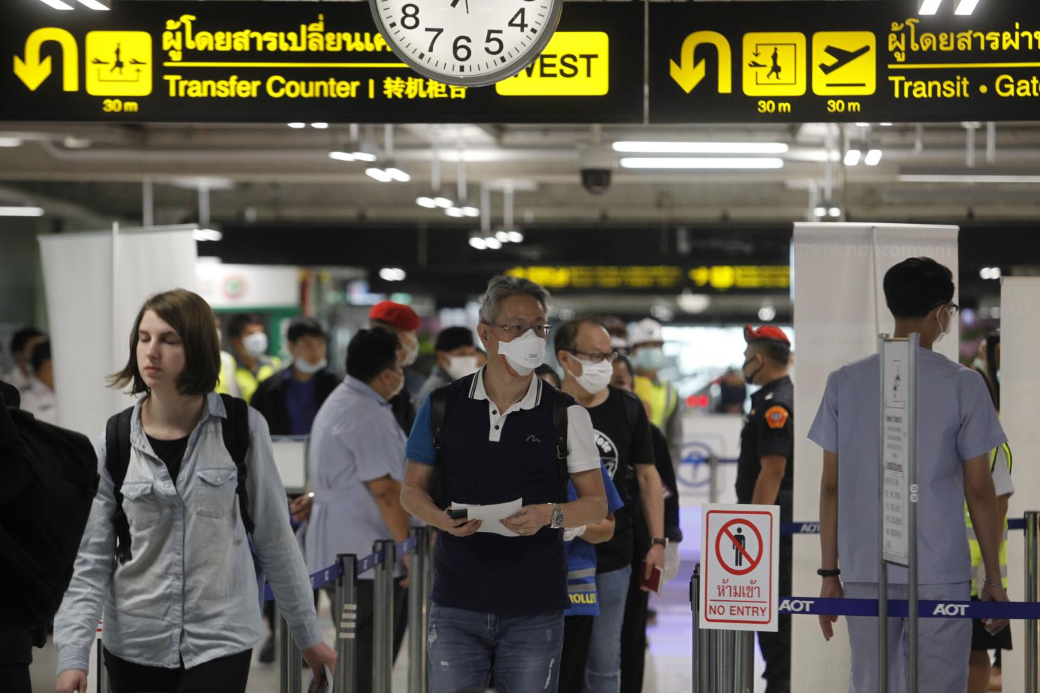 Passengers arriving from several countries including China pass a thermoscan machine at Suvarnabhumi airport as officials introduce precautionary measures against the spread of Covid-19. (Photo by Wichan Charoenkiatpakul)