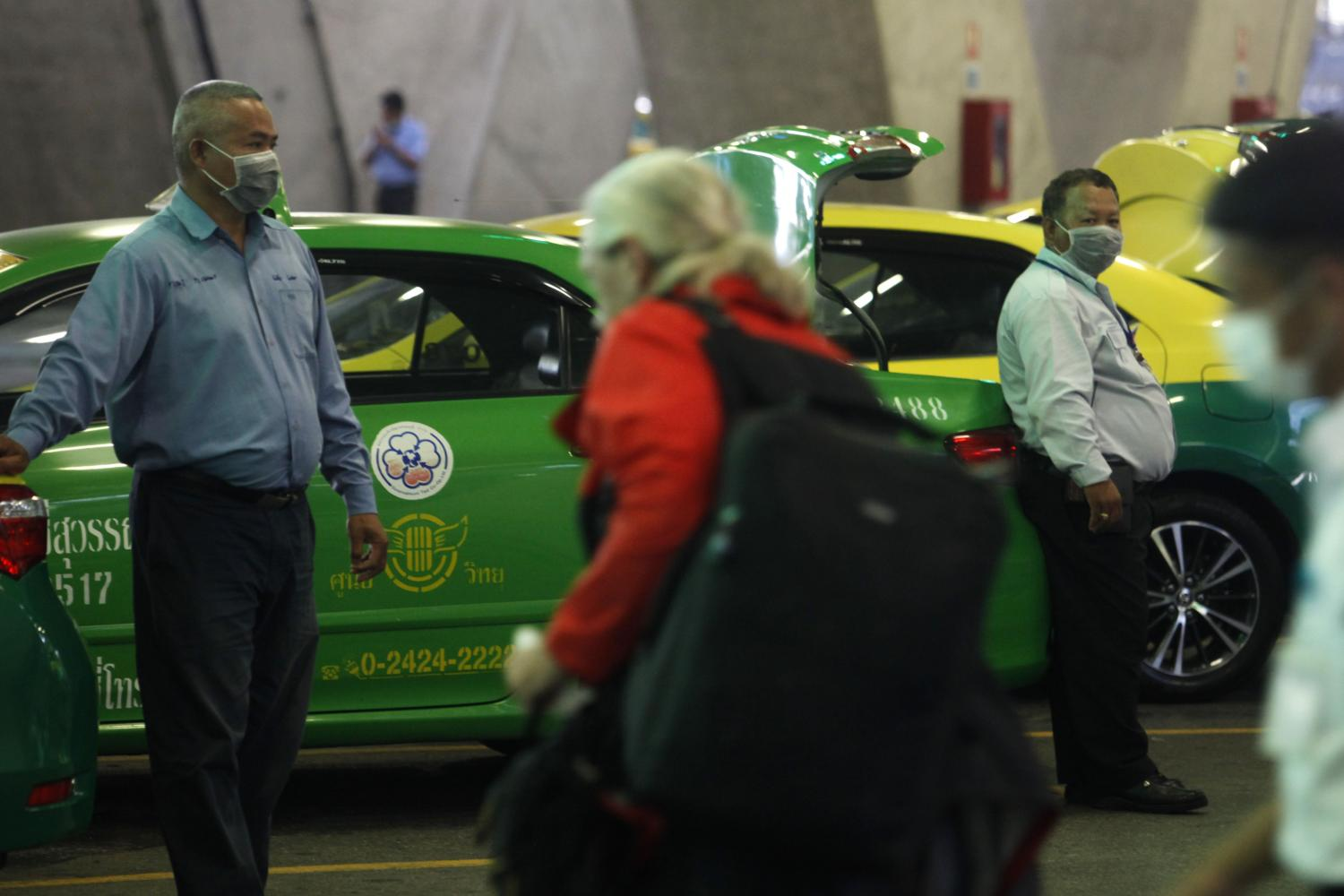 Taxi drivers wait for customers at Suvarnabhumi airport. Self-quarantine required for those infected with Covid-19 or at risk of infection is financially burdensome for low-income earners. (Photo by Wichan Charoenkiatpakul)
