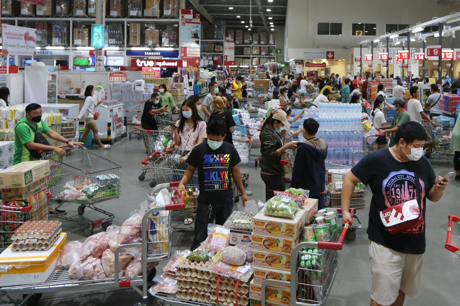 Stocking up: Shoppers form long queues at the Makro wholesale store in Samut Prakan after City Hall yesterday issued an order closing shopping malls and markets in Bangkok and adjacent provinces except those selling food and essential consumer goods for three weeks in an effort to slow the spread of Covid-19.