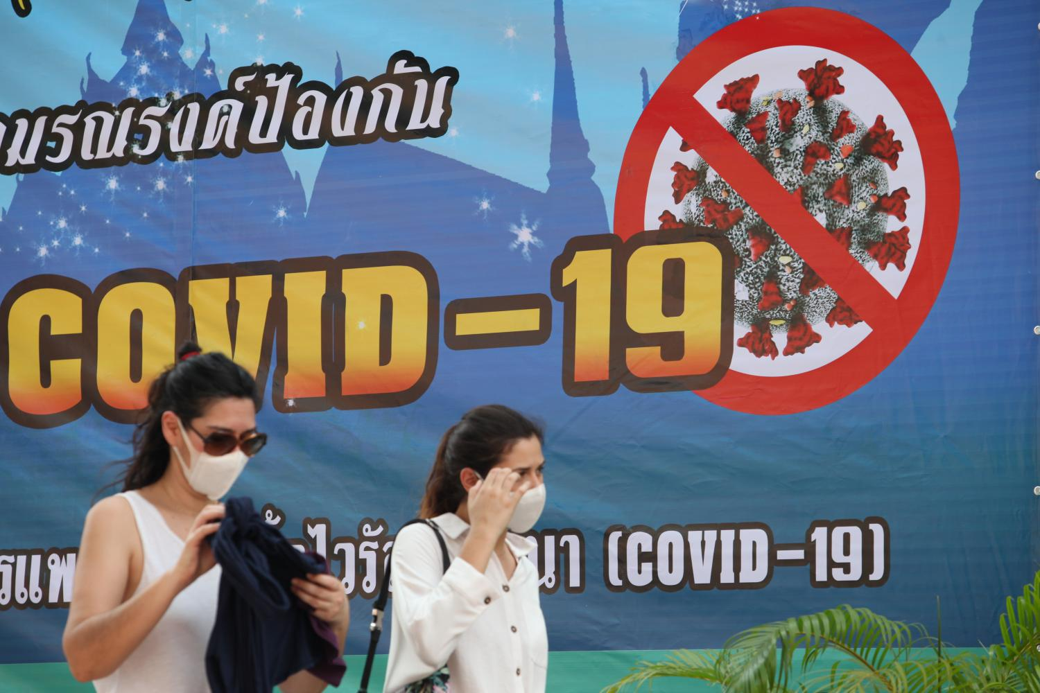 Women wearing face masks walk past a banner explaining how to prevent the spread of Covid-19.Apichart Jinakul