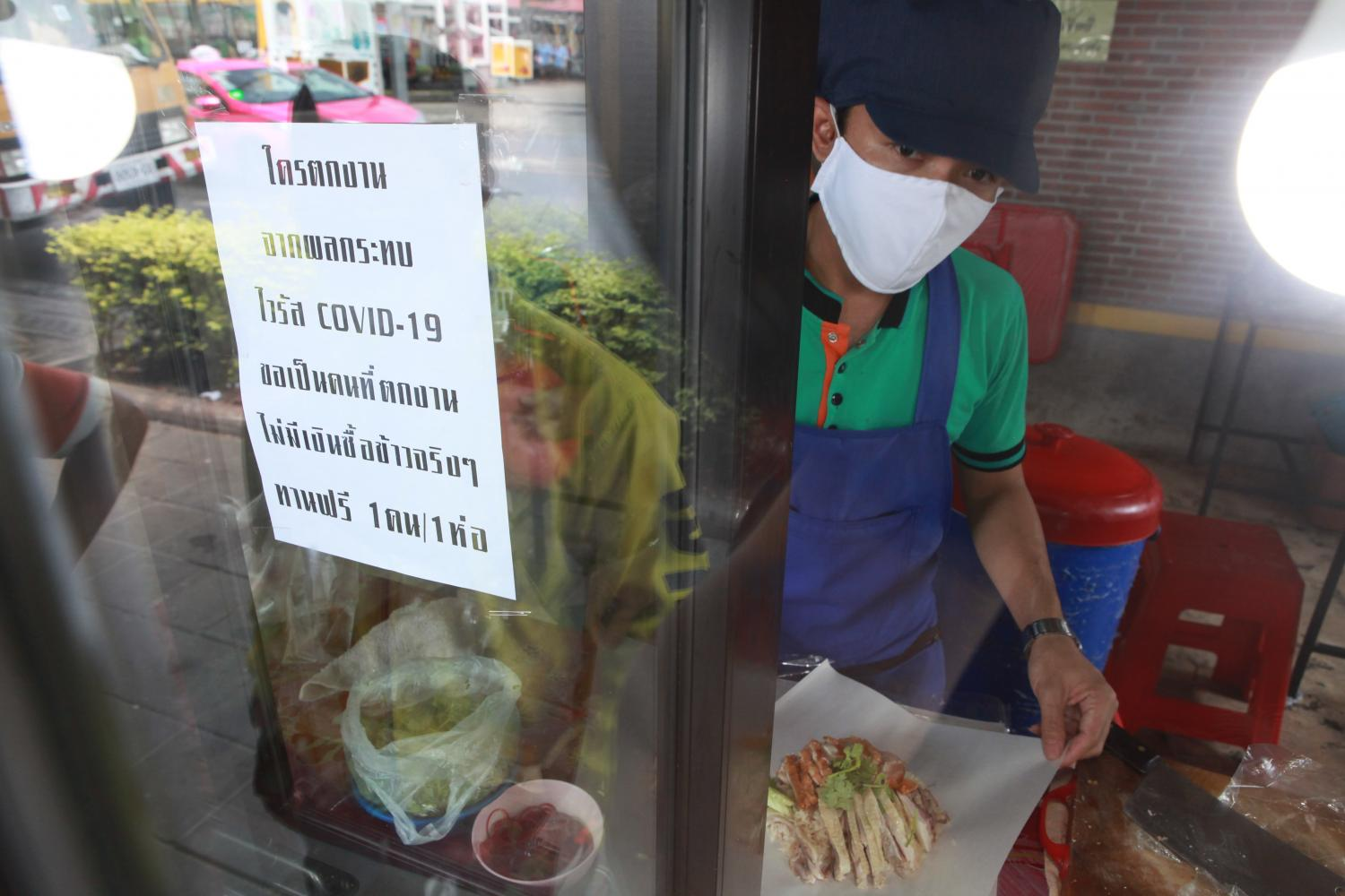 A vendor at an Oshin eatery chain wraps chicken and rice for a customer with a message put up on the stall front offering a free meal to anyone made jobless as a result of the Covid-19 outbreak.