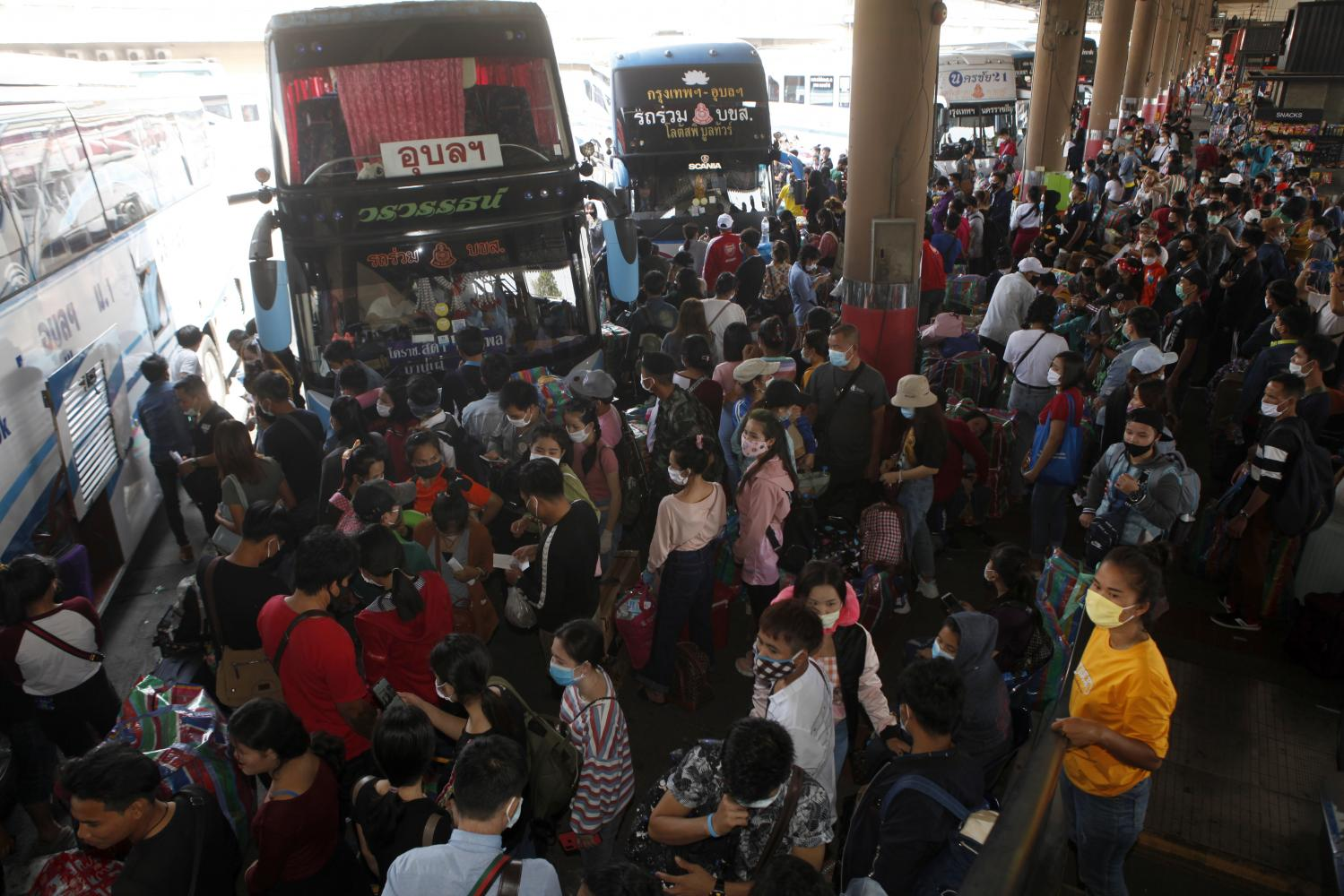 Travellers wait to board their buses at the Mor Chit terminal in Bangkok on Sunday. Migrant workers from Thailand's neighbouring countries are among those reported to have returned home over the weekend. (Nutthawat Wicheanbut)