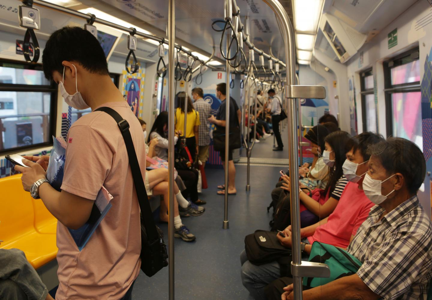 Some passengers on a BTS train wear face masks on Tuesday to protect themselves from Covid-19. From Wednesday onwards the Rail Department strictly requires all rail passengers to wear face masks and leave sufficient space between one another while travelling on a train or at a station. (Photo by Apichit Jinakul)