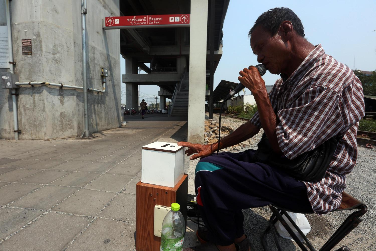 A busker sings a song on a street underneath an elevated train station in Bangkok. Ageing buskers are among those at the lowest rung of society who do not receive social welfare protection from the state. (POST TODAY photo)