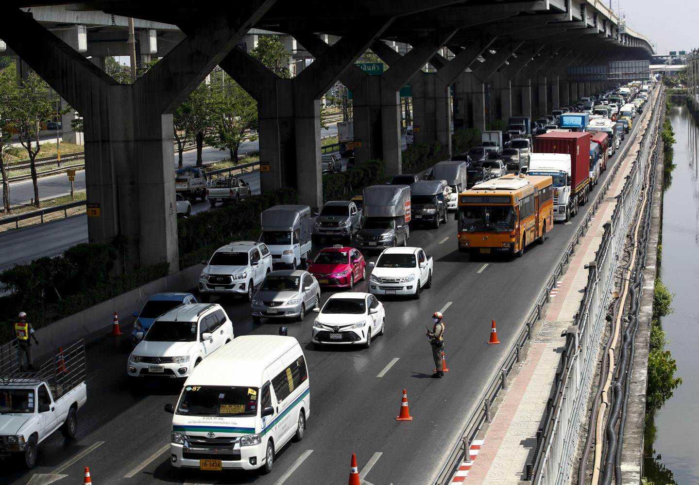 Long lines of vehicles stretch along Vibhavadi Rangsit Road after City Hall set up additional checkpoints to screen people travelling into the city.