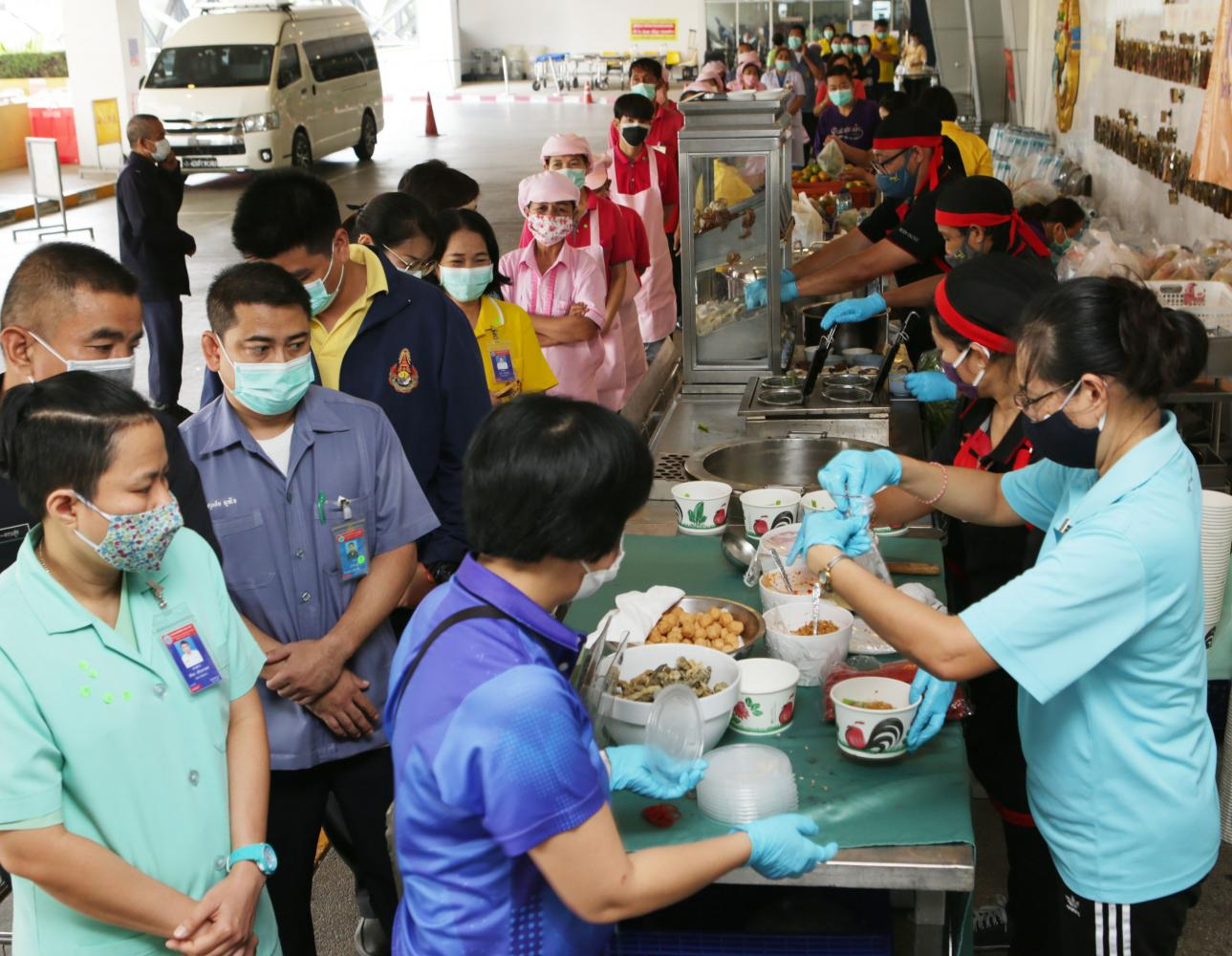 KEEPING UP THEIR STRENGTH: Staff from Suvapee Thammawattana Company which owns the Ying Charoen market in Bang Khen district yesterday set up food stands to cook free food for medical personnel at Bhumibol Adulyadej Hospital. (Photo by Apichit Jinakul)